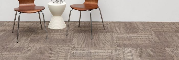 Studio shot of Well Versed model carpet, in a guest area. At the side are two chairs, with a round end table between. A wire sculpture rests on top.