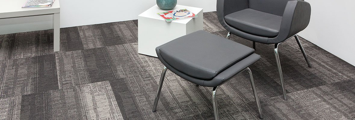 Studio shot of Well Versed model carpeting. The corner of this room contains a plush upholstered chair with matching ottoman. At the side is a white cube end table and a long table placed against the wall.