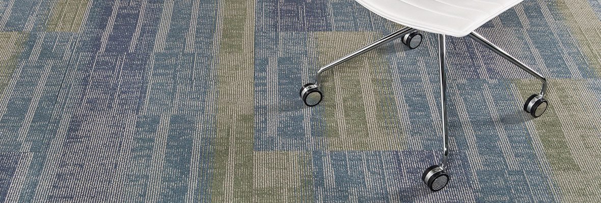 Studio shot of Well Versed model carpet, with palm greens and blues. A rolling office chair is cropped in from the top.