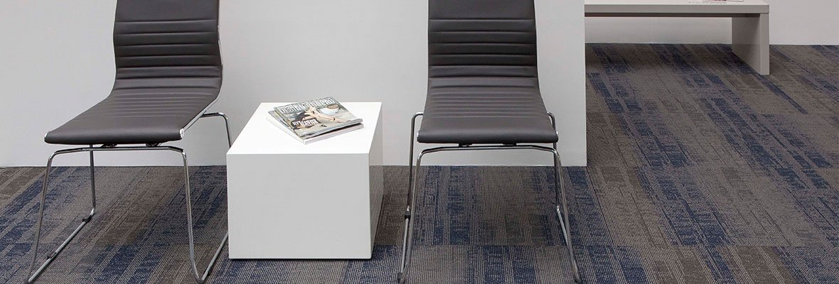 Studio photography, looking into a room lined with Well Versed model carpet squares. Two chairs and cube table have been placed against the wall, with a long cushioned bench against the wall behind.