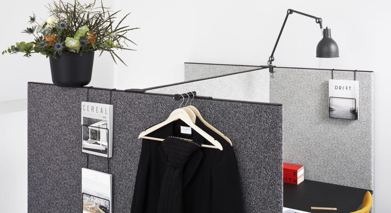 Studio shot of dB privacy screening on a pair of cubicles. Small wire racks hang pamphlets on the outside, next to a business suit hung over the partition.