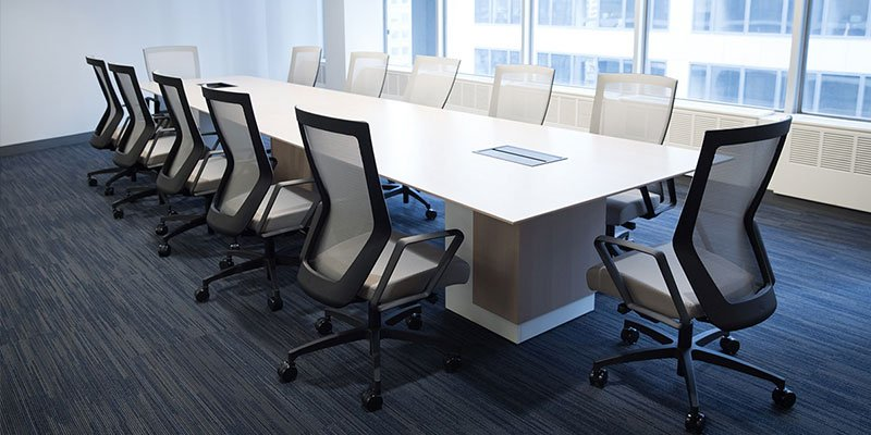 Twelve Run II chairs placed at a long conference table. Each chair has a grey mesh back with matching cushion. Windows overlook the city street, letting light into the room.