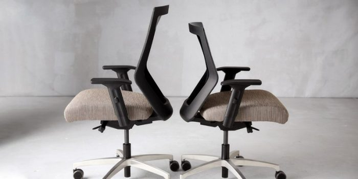 Two RunII chairs, on a grey carpet, placed with their seat backs to eachother. The high-back Run II is on the left, and the mid-back chair is on the right.