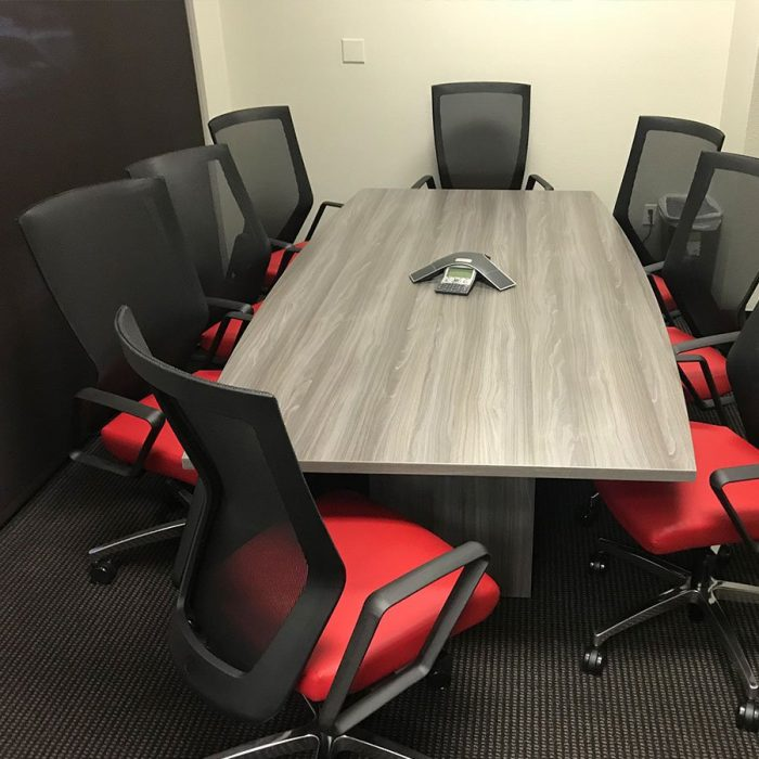 Eight Run II chairs placed at a wooden conference table. Each chair has a black mesh back and a red upholstered seat. A speaker set has been placed in the middle.