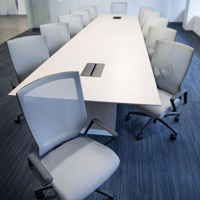 Twelve Run II chairs placed at a long conference table. Each chair has a grey mesh back with matching cushion.
