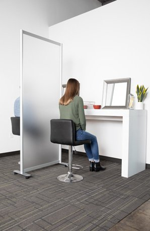 A long desk sits against a wall, with the Split model screen dividing the space between two workers. Two workers are seated on the stool , looking at their work.