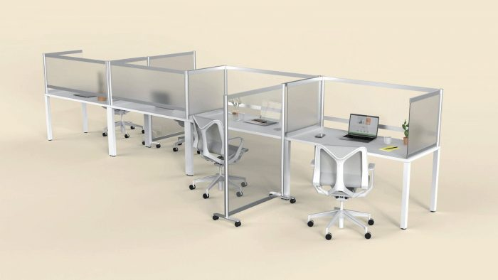 A long desk set for eight office workers. Desk Shields are placed at each seat, with an open laptop on one desk. Between the two nearest seats,a full length Split panel divides two workers.