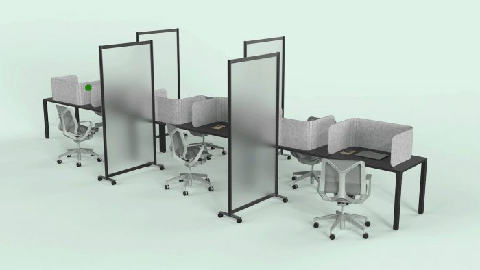 A long wooden table, set up for an office. Each work area is divided with a Hide privacy screen, with the laptop closed in front of it. Each middle seat (of each side of the table) has the Split semi-clear full length privacy screen.