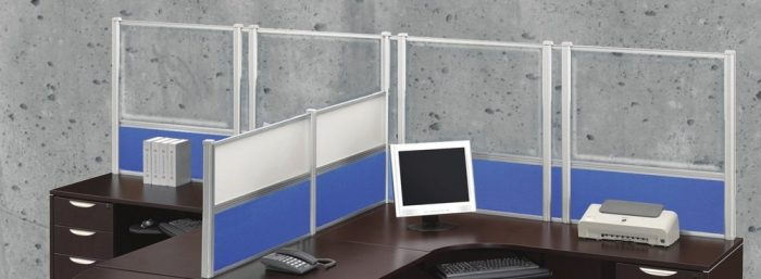 Wide shot of tall Border (model) screens lining the back and sides of two L-shaped desks. Each screen uses clear acrylic, and has a small spacer in between. Two shorter screens divide the desks on the side, with the top panels using frosted acrylic. Each desk has a computer monitor, with a phone at the side.