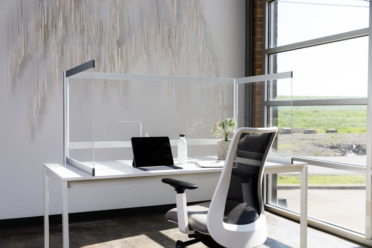 Desk Shield placed at a large window area of an open office. The Desk Shield wraps around the whole desk, and a black laptop is open.
