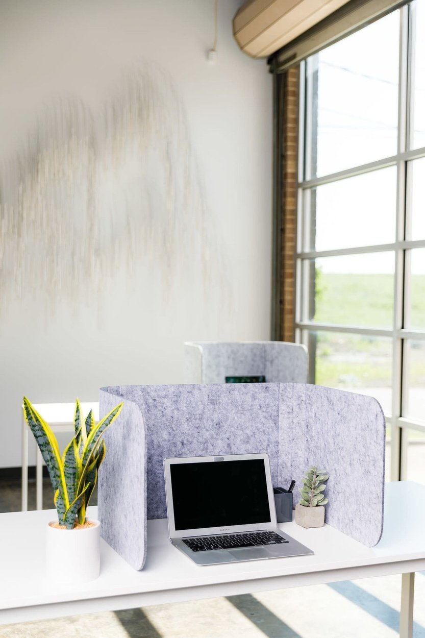 Hide privacy screen placed at a white desk. A smaller table is pushed up against the wall, by the window. It holds another workstation with Hide privacy screen.