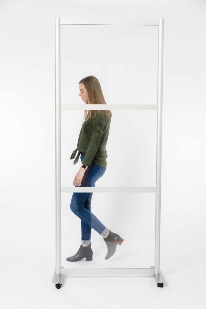 A woman walks by a Split model screen on rolling casters. Her figure is broken up by the Break Style of the acrylic panels.