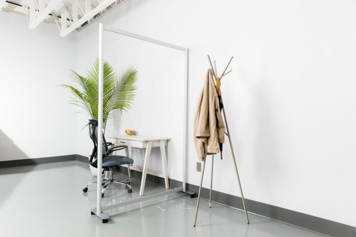 Open style Split model screen at the end of a small work table. On the other side is a tripod-style coatrack.