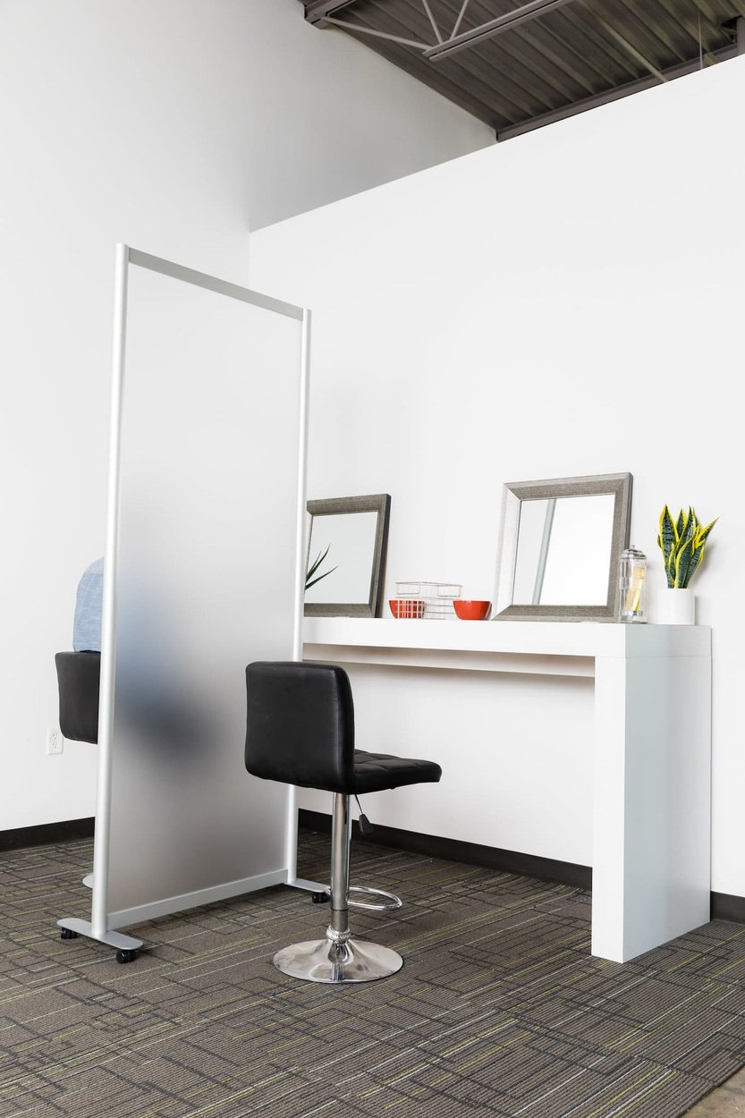 Two workstations side by side. A silver based stool is placed at each side, with a Split frosted acrylic screen in between. There is a framed mirror and plant resting at each work station.