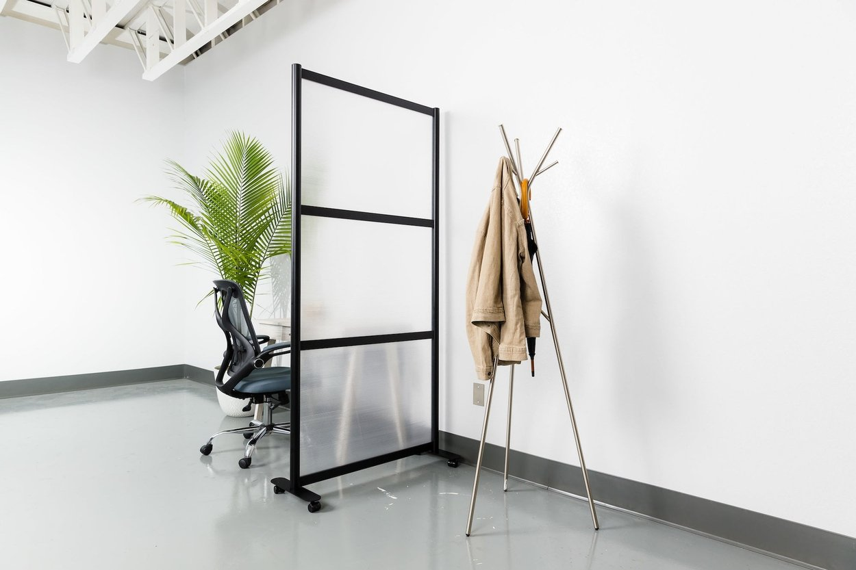 Break style Split model screen at the end of a small work table. It is using a black aluminum frame and frosted acrylic. On the other side is a tripod-style coatrack.